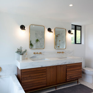 Trendy gray floor and double-sink bathroom photo in Los Angeles with louvered cabinets, medium tone wood cabinets, an undermount tub, white walls, an undermount sink, white countertops and a freestanding vanity