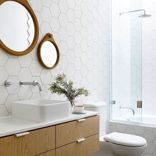This is an example of a contemporary bathroom in Melbourne with an alcove tub, white tile, a vessel sink, flat-panel cabinets, medium wood cabinets, a shower/bathtub combo and a two-piece toilet.