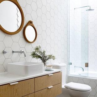 Foto di una stanza da bagno minimal con vasca ad alcova, piastrelle bianche, lavabo a bacinella, ante lisce, ante in legno scuro, vasca/doccia e WC a due pezzi