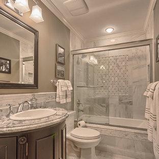 Immagine di una piccola stanza da bagno classica con lavabo da incasso, ante in legno bruno, top in granito, vasca ad alcova, vasca/doccia, WC monopezzo, piastrelle bianche, piastrelle in pietra, pareti verdi, pavimento in marmo e consolle stile comò