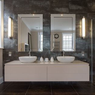 This is an example of a contemporary bathroom in London with a vessel sink, flat-panel cabinets, white cabinets and brown walls.