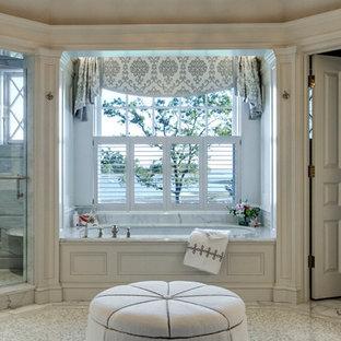 Immagine di una stanza da bagno padronale classica con ante con riquadro incassato, ante bianche, vasca idromassaggio, doccia aperta, WC monopezzo, pareti bianche, pavimento con piastrelle in ceramica, lavabo sottopiano e top in granito
