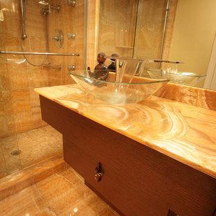 マイアミの中サイズのコンテンポラリースタイルのおしゃれなバスルーム (浴槽なし) (フラットパネル扉のキャビネット、中間色木目調キャビネット、アルコーブ型シャワー、オレンジのタイル、オレンジの壁、大理石の床、ベッセル式洗面器、オニキスの洗面台、オレンジの床、引戸のシャワー、オレンジの洗面カウンター) の写真