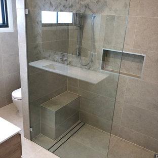 Diseño de cuarto de baño principal y casetón, moderno, de tamaño medio, con puertas de armario marrones, ducha abierta, sanitario de una pieza, baldosas y/o azulejos de porcelana, paredes beige, suelo de baldosas de porcelana, suelo beige, ducha abierta y encimeras blancas