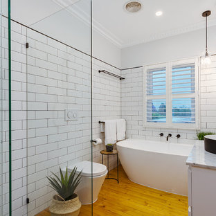 Photo of a contemporary bathroom in Melbourne with flat-panel cabinets, white cabinets, a freestanding tub, an open shower, a wall-mount toilet, white tile, white walls, light hardwood floors, a vessel sink, brown floor, an open shower and white benchtops.