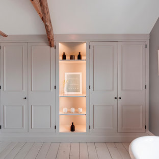 Inspiration for a medium sized country ensuite bathroom in Devon with beaded cabinets, grey cabinets, a freestanding bath, a corner shower, white tiles, metro tiles, grey walls, painted wood flooring, a built-in sink, grey floors, an open shower and a two-piece toilet.