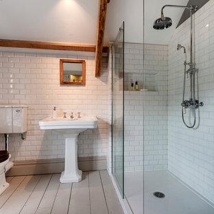 Ejemplo de cuarto de baño de estilo de casa de campo, de tamaño medio, con ducha esquinera, sanitario de dos piezas, baldosas y/o azulejos blancos, baldosas y/o azulejos de cemento, paredes grises, suelo de madera pintada, suelo gris, ducha abierta y lavabo con pedestal