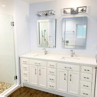 Ejemplo de cuarto de baño principal, tradicional renovado, grande, con armarios con paneles lisos, puertas de armario blancas, bañera esquinera, ducha empotrada, baldosas y/o azulejos blancos, baldosas y/o azulejos de cemento, paredes púrpuras, suelo de madera en tonos medios, encimera de mármol, suelo marrón, ducha con puerta con bisagras y encimeras blancas