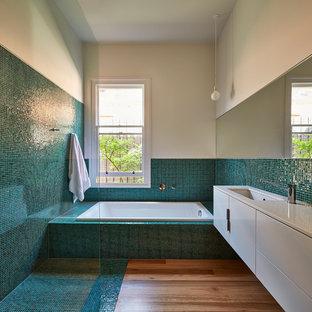 Modelo de cuarto de baño contemporáneo con armarios con paneles lisos, puertas de armario blancas, bañera encastrada, ducha a ras de suelo, baldosas y/o azulejos azules, baldosas y/o azulejos verdes, baldosas y/o azulejos en mosaico, lavabo bajoencimera, suelo de madera en tonos medios, suelo turquesa y ducha abierta