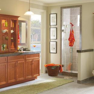 Corner shower - large traditional master gray tile and ceramic tile ceramic tile corner shower idea in Indianapolis with shaker cabinets, medium tone wood cabinets, a one-piece toilet, beige walls, an undermount sink and limestone countertops