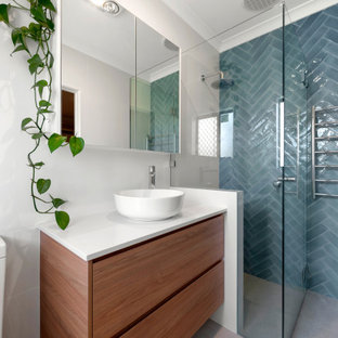 This is an example of a mid-sized contemporary master bathroom in Perth with medium wood cabinets, a corner tub, a corner shower, a one-piece toilet, blue tile, ceramic tile, white walls, ceramic floors, a vessel sink, beige floor, a hinged shower door and white benchtops.