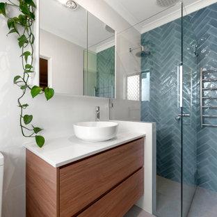Mittelgroßes Modernes Badezimmer En Suite mit hellbraunen Holzschränken, Eckbadewanne, Eckdusche, Toilette mit Aufsatzspülkasten, blauen Fliesen, Keramikfliesen, weißer Wandfarbe, Keramikboden, Aufsatzwaschbecken, beigem Boden, Falttür-Duschabtrennung und weißer Waschtischplatte in Perth