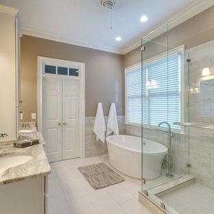 アトランタの広いトランジショナルスタイルのおしゃれなマスターバスルーム (アンダーカウンター洗面器、落し込みパネル扉のキャビネット、白いキャビネット、置き型浴槽、ベージュのタイル、磁器タイル、ベージュの壁、磁器タイルの床、分離型トイレ、珪岩の洗面台、白い床、開き戸のシャワー、白い洗面カウンター、洗面台2つ、造り付け洗面台、コーナー設置型シャワー) の写真