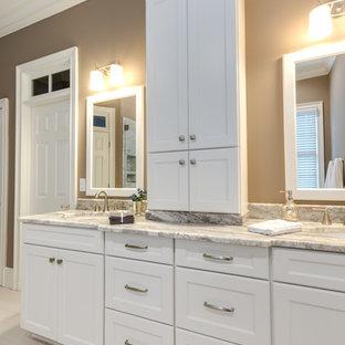 アトランタの広いトランジショナルスタイルのおしゃれなマスターバスルーム (アンダーカウンター洗面器、落し込みパネル扉のキャビネット、白いキャビネット、置き型浴槽、ベージュのタイル、磁器タイル、ベージュの壁、磁器タイルの床、珪岩の洗面台、白い床、開き戸のシャワー、白い洗面カウンター、トイレ室、洗面台2つ、造り付け洗面台、コーナー設置型シャワー、分離型トイレ) の写真