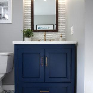 プロビデンスの小さいトランジショナルスタイルのおしゃれな浴室 (家具調キャビネット、青いキャビネット、分離型トイレ、白いタイル、磁器タイル、グレーの壁、磁器タイルの床、アンダーカウンター洗面器、珪岩の洗面台、マルチカラーの床、白い洗面カウンター) の写真