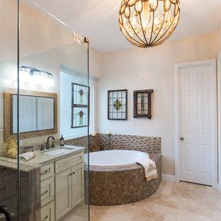ダラスの中サイズのトランジショナルスタイルのおしゃれなマスターバスルーム (家具調キャビネット、ヴィンテージ仕上げキャビネット、コーナー型浴槽、コーナー設置型シャワー、茶色いタイル、ベージュの壁、トラバーチンの床、御影石の洗面台、ベージュの床、開き戸のシャワー、分離型トイレ、磁器タイル、アンダーカウンター洗面器) の写真