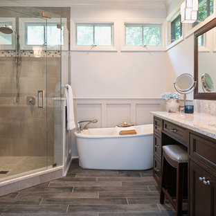 Example of a mid-sized arts and crafts master gray tile and porcelain tile porcelain tile bathroom design in Charlotte with beaded inset cabinets, dark wood cabinets, a two-piece toilet, blue walls, an undermount sink and quartz countertops
