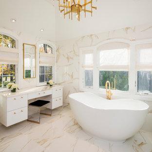 Foto på ett stort funkis vit en-suite badrum, med släta luckor, vita skåp, ett fristående badkar, en hörndusch, vit kakel, marmorkakel, vita väggar, marmorgolv, marmorbänkskiva, vitt golv och dusch med gångjärnsdörr