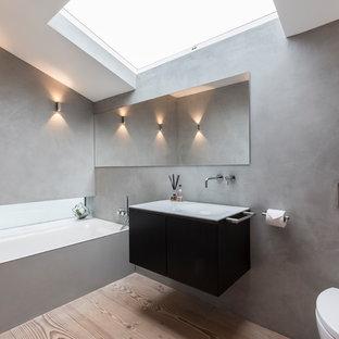 Immagine di una stanza da bagno con doccia moderna di medie dimensioni con nessun'anta, ante grigie, doccia aperta, WC monopezzo, pareti grigie, pavimento in cemento, lavabo da incasso, top in cemento, pavimento grigio, doccia aperta e vasca sottopiano