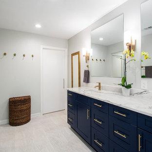 Cette photo montre une grande salle de bain principale tendance avec un placard à porte plane, des portes de placard bleues, une douche double, un carrelage gris, des carreaux de béton, un lavabo encastré, un plan de toilette en marbre, une cabine de douche à porte battante, un plan de toilette blanc, un WC séparé, un mur gris, un sol en carrelage de porcelaine et un sol beige.