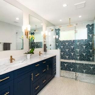 Пример оригинального дизайна интерьера: большая главная ванная комната в стиле современная классика с синими фасадами, цементной плиткой, серыми стенами, полом из керамогранита, врезной раковиной, мраморной столешницей, бежевым полом, душем с распашными дверями, белой столешницей, фасадами в стиле шейкер, душем в нише и синей плиткой
