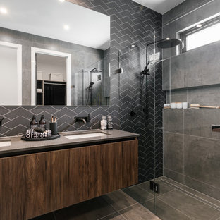 This is an example of a contemporary master bathroom in Adelaide with a hinged shower door, flat-panel cabinets, dark wood cabinets, a curbless shower, black tile, an undermount sink, grey floor and grey benchtops.