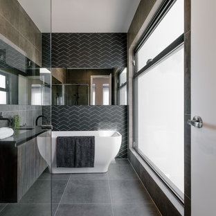 Photo of a contemporary bathroom in Adelaide with flat-panel cabinets, dark wood cabinets, a freestanding tub, black tile, an undermount sink, grey floor, an open shower and black benchtops.