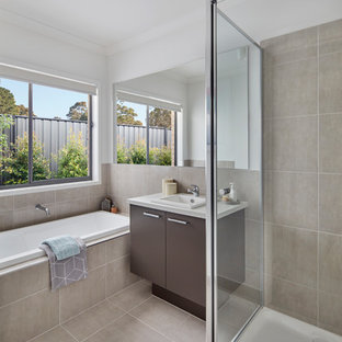 Inspiration for a contemporary master bathroom in Melbourne with flat-panel cabinets, brown cabinets, a drop-in tub, a corner shower, beige tile, beige walls, a drop-in sink and beige floor.