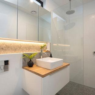 На фото: маленькая ванная комната в современном стиле с белыми фасадами, белой плиткой, керамической плиткой, белыми стенами, полом из терраццо, столешницей из дерева, открытым душем, душем без бортиков, серым полом и коричневой столешницей