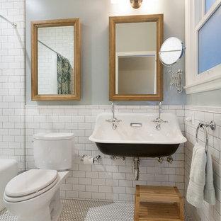 Bild på ett litet vintage badrum, med ett avlångt handfat, ett badkar i en alkov, en dusch/badkar-kombination, en toalettstol med separat cisternkåpa, vit kakel, keramikplattor, grå väggar och klinkergolv i keramik