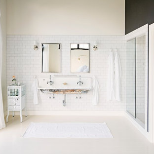 Industrial bathroom in Portland with a trough sink, white tile, subway tile and multi-coloured walls.