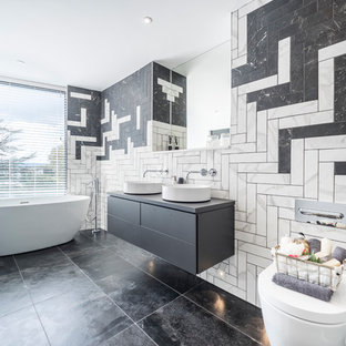 Large contemporary bathroom in Dorset with flat-panel cabinets, grey cabinets, a freestanding bath, a wall mounted toilet, black and white tiles, grey worktops, white walls, a vessel sink and black floors.
