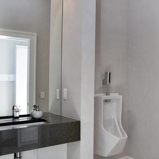 Idee per una grande stanza da bagno padronale moderna con nessun'anta, orinatoio, pareti grigie, lavabo sottopiano e top in quarzite