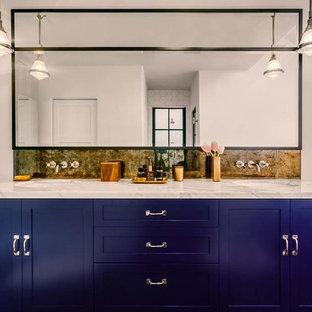 Foto de cuarto de baño principal, ecléctico, grande, con lavabo encastrado, armarios estilo shaker, puertas de armario azules, encimera de mármol, baldosas y/o azulejos con efecto espejo, paredes blancas y suelo de madera oscura