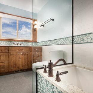 Ispirazione per una stanza da bagno rustica di medie dimensioni con lavabo da incasso, vasca da incasso, piastrelle verdi, piastrelle di vetro, WC monopezzo, ante a filo, ante in legno scuro, vasca/doccia, pareti blu, pavimento in ardesia e top in granito