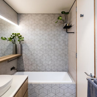 Modern bathroom in Perth with medium wood cabinets, a drop-in tub, grey walls, cement tiles, a vessel sink, grey floor, white benchtops, an open shower, ceramic tile, an open shower and a single vanity.