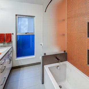 Idéer för att renovera ett funkis grå grått badrum, med ett undermonterad handfat, släta luckor, vita skåp, ett badkar i en alkov, en dusch/badkar-kombination, orange kakel, mosaik och vita väggar