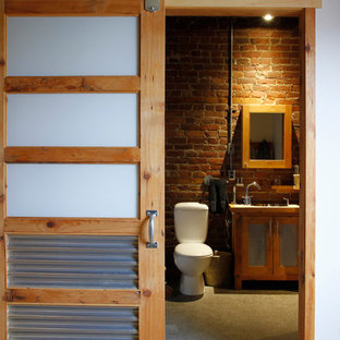Bathroom - industrial bathroom idea in Montreal with glass-front cabinets