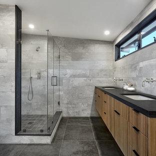 Exempel på ett 60 tals svart svart badrum, med släta luckor, skåp i mellenmörkt trä, en hörndusch, grå kakel, ett undermonterad handfat, grått golv och dusch med gångjärnsdörr
