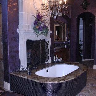 Idee per una stanza da bagno padronale mediterranea di medie dimensioni con ante in legno bruno, piastrelle beige, top in marmo, vasca da incasso, lastra di pietra, pareti viola e pavimento in pietra calcarea