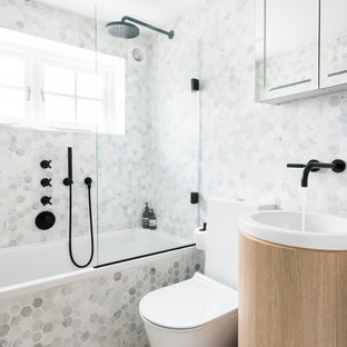 Photo of a contemporary bathroom in London with a built-in bath, a shower/bath combination, a one-piece toilet, multi-coloured tiles, mosaic tiles, a pedestal sink and beige floors.