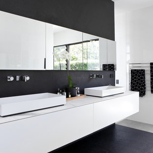 Design ideas for a contemporary master bathroom in Sunshine Coast with flat-panel cabinets, white cabinets, black tile, mosaic tile, white walls, mosaic tile floors, a vessel sink, black floor and white benchtops.