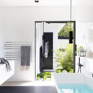 Inspiration for a modern master bathroom in Sunshine Coast with flat-panel cabinets, white cabinets, a freestanding tub, an open shower, black tile, white tile, glass tile, white walls, a vessel sink, black floor, an open shower and white benchtops.