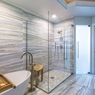Diseño de cuarto de baño principal, moderno, grande, con bañera exenta, ducha empotrada, baldosas y/o azulejos grises, baldosas y/o azulejos de piedra, paredes negras y suelo de baldosas de porcelana