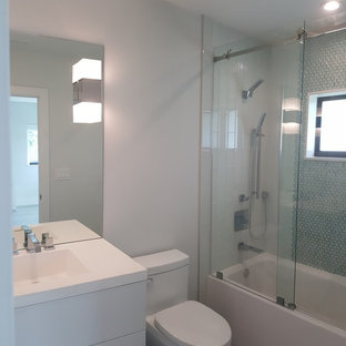Идея дизайна: ванная комната среднего размера в стиле модернизм с плоскими фасадами, белыми фасадами, ванной в нише, душем над ванной, унитазом-моноблоком, серой плиткой, металлической плиткой, серыми стенами, мраморным полом, монолитной раковиной, столешницей из искусственного камня, серым полом и душем с раздвижными дверями