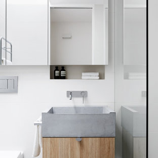 Photo of a small contemporary master bathroom in Melbourne with open cabinets, grey cabinets, a curbless shower, a wall-mount toilet, white tile, ceramic tile, white walls, ceramic floors, a wall-mount sink, concrete benchtops, grey floor, an open shower and grey benchtops.