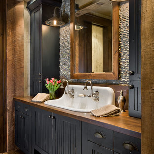 Modelo de cuarto de baño rústico con puertas de armario azules, lavabo de seno grande, encimera de madera y encimeras marrones
