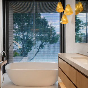 This is an example of a contemporary bathroom in Sydney with flat-panel cabinets, a freestanding tub, white tile, white walls, a drop-in sink, white floor, beige benchtops and medium wood cabinets.