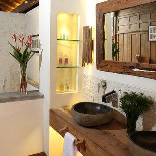 Idee per una stanza da bagno tropicale con lavabo a bacinella, top in legno e top marrone
