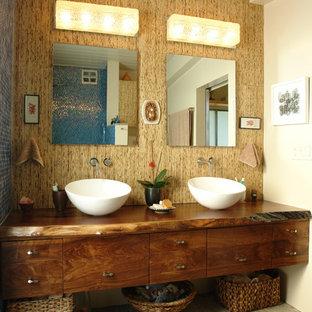 Immagine di una grande stanza da bagno padronale tropicale con lavabo a bacinella, top in legno, piastrelle blu, piastrelle di vetro, pareti marroni, pavimento con piastrelle di ciottoli, ante lisce e ante in legno bruno